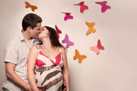 Young caucasian pregnant couple kissing near the wall with paper butterflies photo