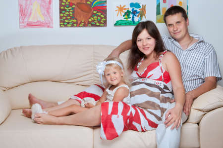 happy beautiful smiling young family on sofa in home