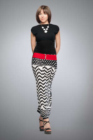 Beautiful fashionable woman in black top and black and white skirt with red belt. Studio shot.