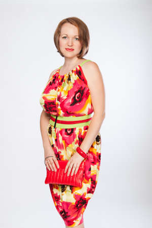Beautiful fashionable woman in multicoloured dress. Studio shot. Stock Photo