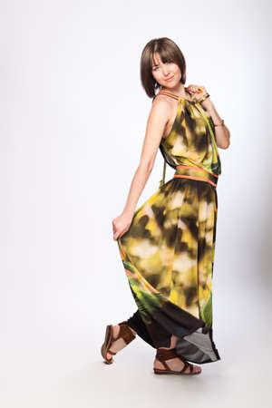 Beautiful fashionable woman in green dress. Studio shot.