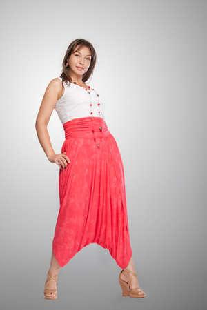 Beautiful fashionable woman in pink wide trousers. Studio shot.