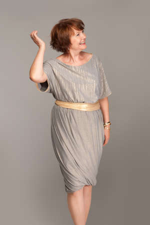 Beautiful fashionable mature woman in grey dress. Studio shot.