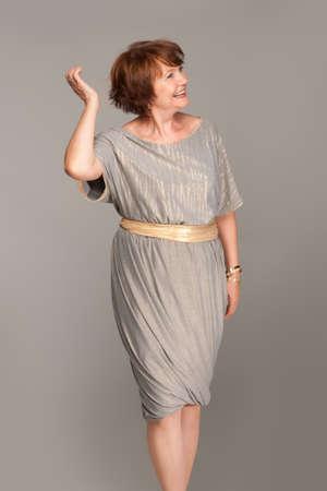 Beautiful fashionable mature woman in grey dress. Studio shot.