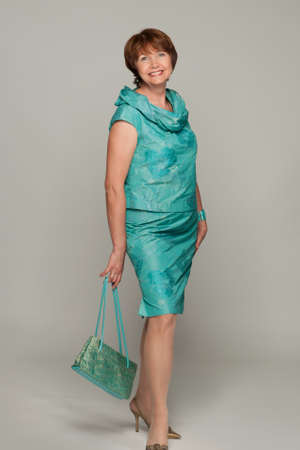 sexy mature women: Beautiful fashionable mature woman in turquoise costume. Studio shot. Stock Photo