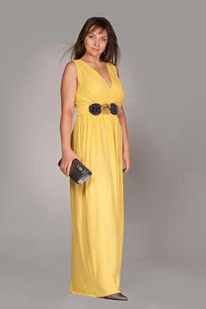 Beautiful fashionable woman in long yellow dress. Studio shot.