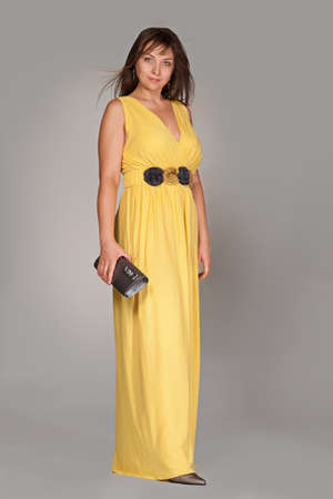 Beautiful fashionable woman in long yellow dress. Studio shot.