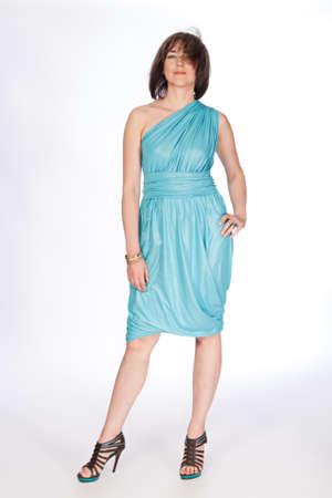 Beautiful fashionable woman in turquoise dress. Studio shot.