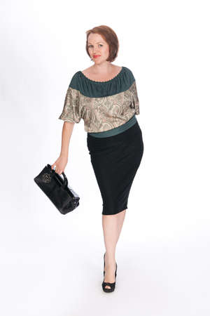 Beautiful fashionable woman wearing green blouse and black skirt with black bag in her hand. Studio shot. Stock Photo