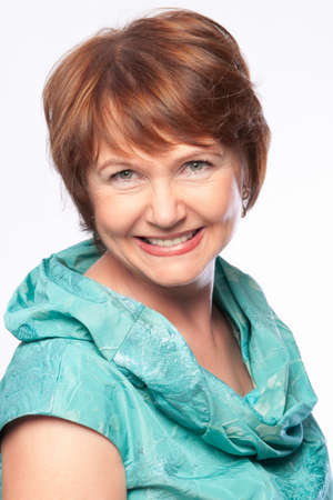 Beautiful fashionable smiling mature woman in turquoise costume head and shouders portrait. Studio shot.