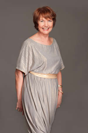 Happy beautiful fashionable mature woman in grey dress. Studio shot. Stock Photo