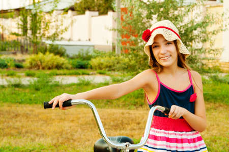 Happy beautiful girl with her bicycle near home on sunset half-length portrait Stock Photo