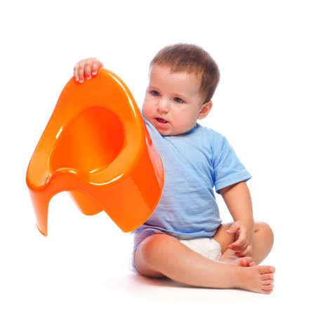 Funny little boy playing with the orange potty studio portrait  isolated on white background  photo