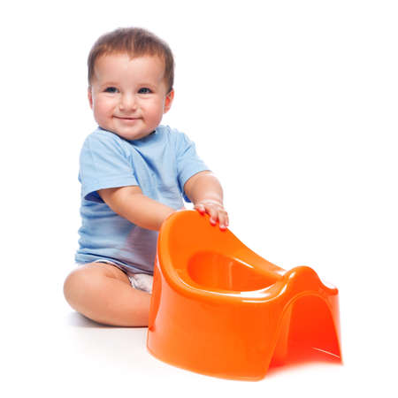 Happy little boy playing with orange potty studio portrait (isolated on white background)