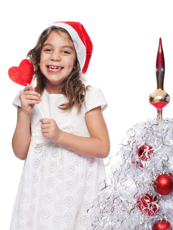 Color photo of a happy five years old girl wearing santa hat with heart form lollipop in her hands while standing by a white decorated Christmas tree. Shot isolated on white background.