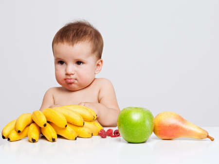 Baby boy indoor portrait with fruits on the table. Healthy eating concept.