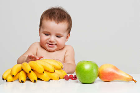 Happy baby boy indoor portrait with fruits on the table. Healthy eating concept.