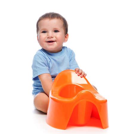 Happy little boy playing with orange potty studio portrait (isolated on white background)