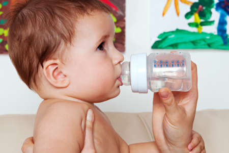 Mother giving the water from bottle to baby at home Stock Photo