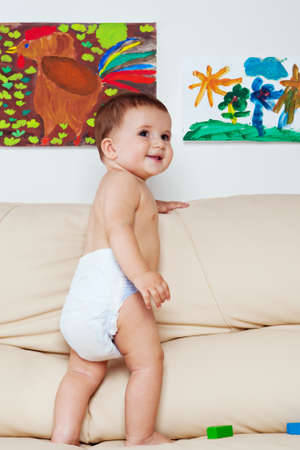Happy baby boy standing on the sofa lifestyle portrait photo