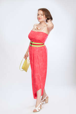 Happy beautiful fashionable mid woman in pink dress on white background studio shot