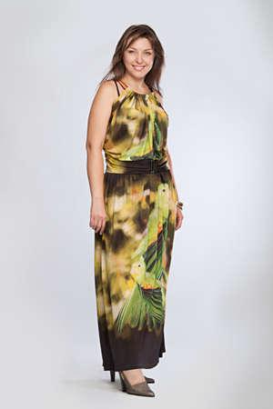 Happy beautiful fashionable mid aged woman in green dress. Studio shot.