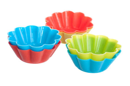 Orange, blue and green silicone baking cups for muffins or cupcake isolated on white background Stock Photo