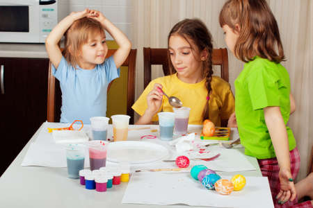 three people only: Three little girls (sisters) painting on Easter eggs at home kitchen