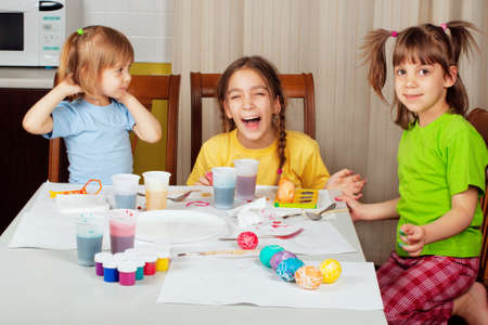 Three little girls (sisters) painting on Easter eggs at home kitchen