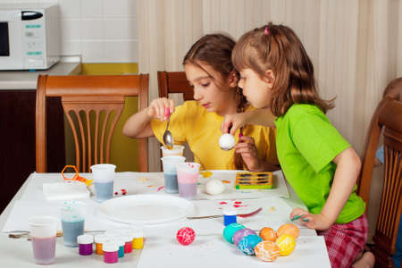 Two little girls (sisters) painting on Easter eggs at home kitchen