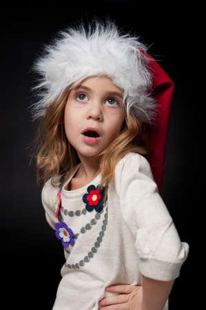 Beautiful fashionable little girl wearing Santa hat studio portrait  black background