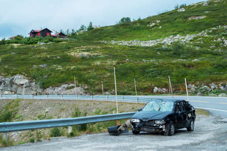 crushed car near mountain road in Norway Editorial