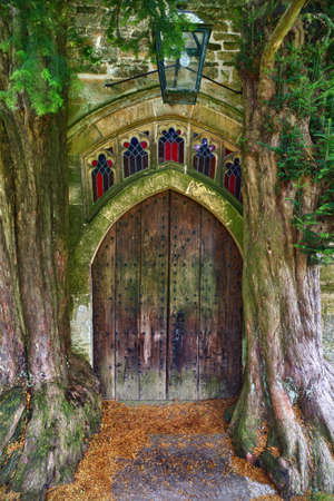 gloucestershire: Wooden Door of St Edwards church with two ancient yew trees, Stow-on-the-wold, Cotswolds, UK