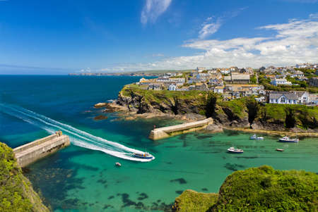 Cove and harbour of Port Isaac with arriving ship, Cornwall, England
