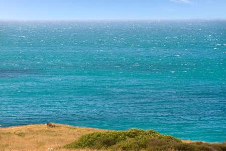far off: Bench on cliff next to sea, Cornwall, England Stock Photo