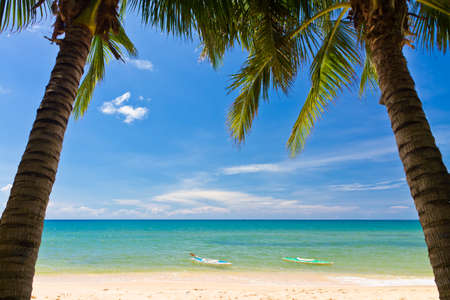 far off: Sand beach with palms and canoes in Phu Quoc close to Duong Dong, Vietnam Stock Photo