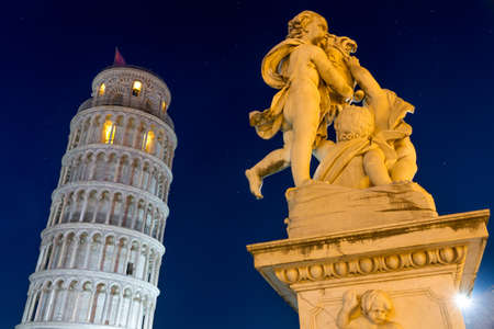 Leaning Tower of Pisa with statue after sunset, Tuscany, Italy