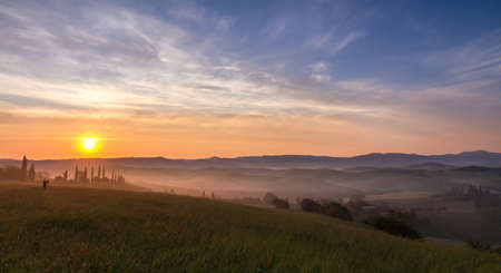 Val d Orcia after sunrise with photographer, Tuscany, Italy photo