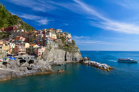 Village of Manarola with ferry, Cinque Terre, Italy photo