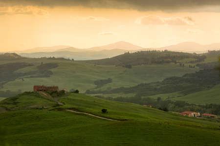 Tuscany landscape with farmhouse and yellow sky, Pienza, Italy