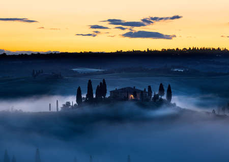 toscana: Tuscany farmhouse in morning mist with yellow skies, Val d