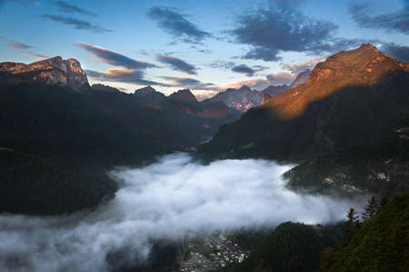 far off: Valley in Dolomites with early morning clouds, Alps, Italy