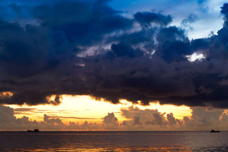 far off: Sunset at South China Sea with threatening sky and ships, Phu Quoc, Vietnam