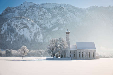 schwangau: St. Coloman with trees in wintery landscape, Alps, Germany Stock Photo