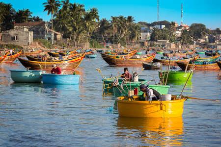 fishing village: MUI NE, VIETNAM - FEBRUARY 08 - Fishermen in traditional small fishing boats Editorial