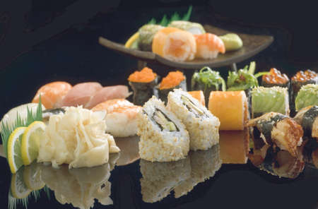 sake maki: Fresh and delicious maki and nigiri sushi and sake on the black glass. Stock Photo