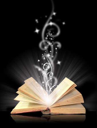 Open book on a black background with magical light.