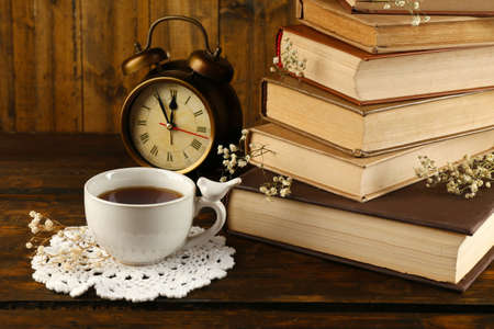 Cup of tea with books and clock on wooden background Stock Photo