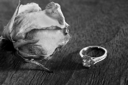 Diamond ring next to a dried rose.