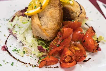 A dish of sicilian rolls, tomatoes and orange, made of phyllo dough